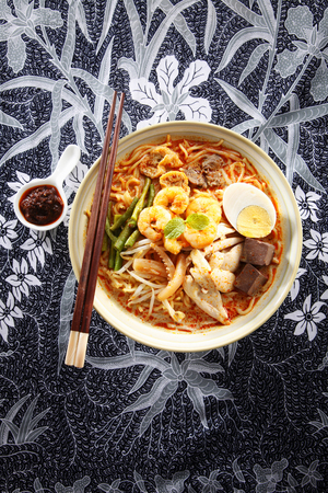 malaysian food bowl of the curry noodle rest on batik Stock Photo