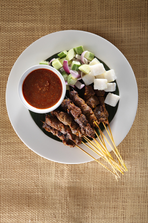 top view of malaysian food satay on the plate with the cucumber and keupat