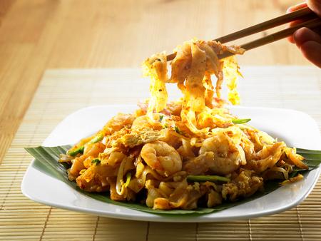 chop stick picking up malaysian famous food Penang fried kuey teow