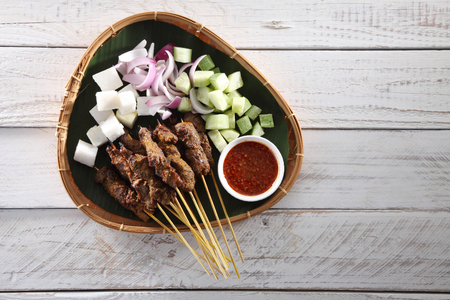 Malaysian famous food satay on bamboo basket with the cucumber and keupat Imagens