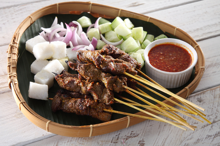 Malaysian famous food satay on bamboo basket with the cucumber and keupat Archivio Fotografico