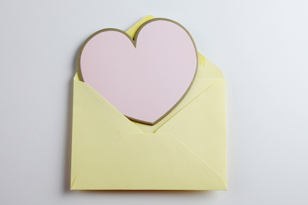 Heart shaped note in envelope onthe plain background