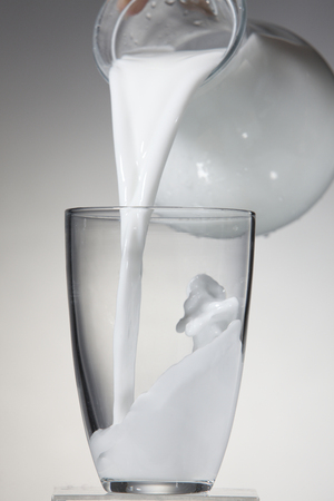 Jug of milk bring poured into a glass. Stock fotó