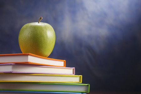 An apple on a stack of books.