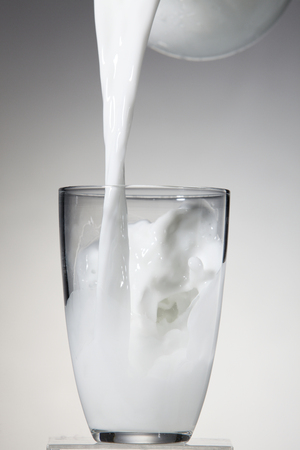Jug of milk bring poured into a glass. Imagens