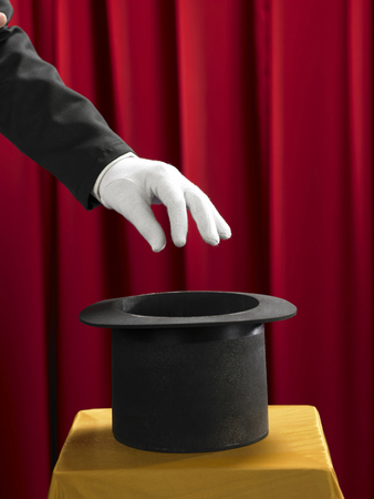 Hands of the magician with top hat on stage. Imagens - 117871406