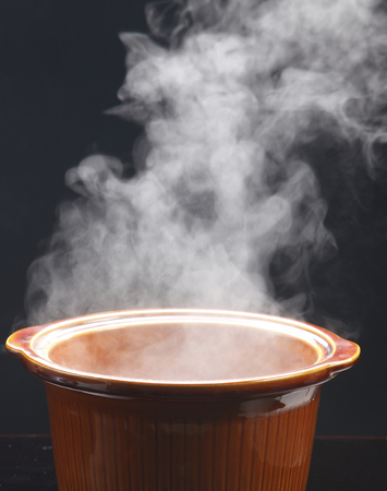 Brown cooking pot with steam on dark background. Imagens
