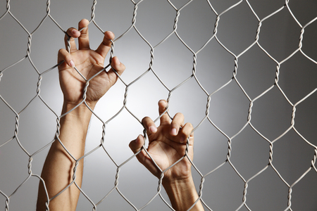 depression - close up of hand on chain-link fence. Stock Photo