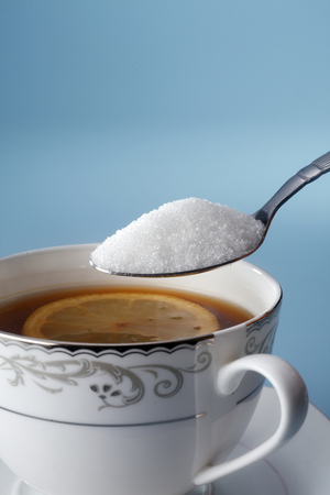 stock image of adding sugar to tea