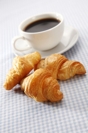 Croissant and Coffee on Checked Table Cloth on a Table Top