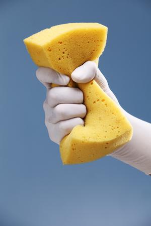 Main avec un gant de protection en caoutchouc blanc tenant une éponge jaune.