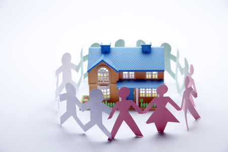 Paper people holding hands together surrounding a house.