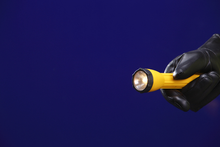 male hand holding lit flashlight  at night Stok Fotoğraf