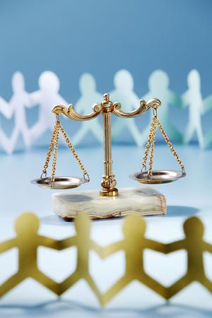 Paper chain  surrounding a balance scale. Reklamní fotografie