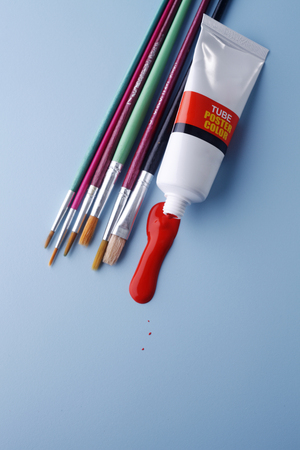 Multiple paintbrushes with a tube of paint isolated on blue background.