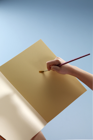 Human hand preparing to draw on a sketch pad. Banco de Imagens