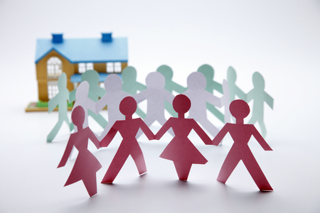 Paper people holding hands together near a house. Stock Photo
