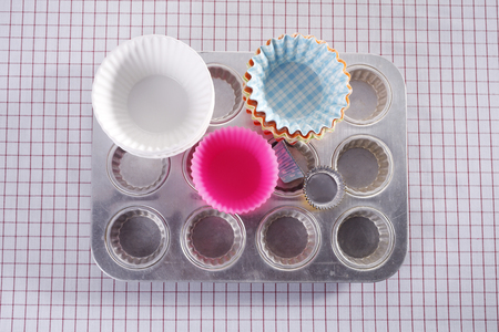 Cupcake molds isolated on picnic cloth.
