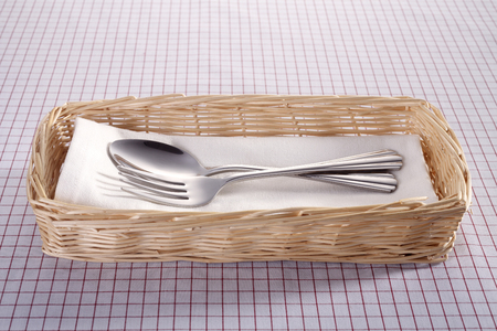 Fork and spoon in a rattan basket. Banco de Imagens