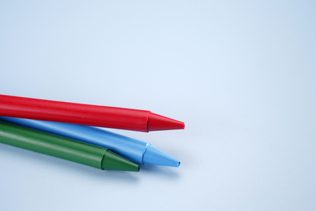 Three crayons isolated on the blue background.