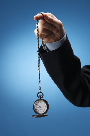 Human hand swinging a pocketwatch. Stock Photo