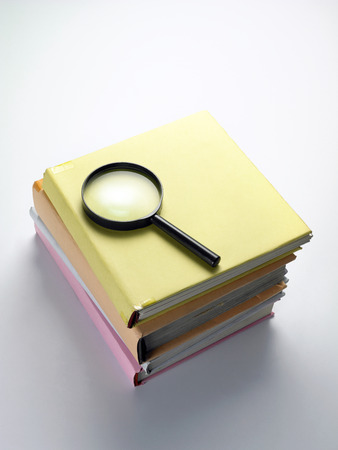 magnifying glass on top of books