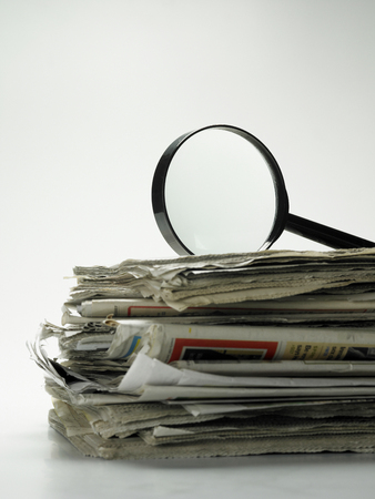 magnifying glass on top of newspaper