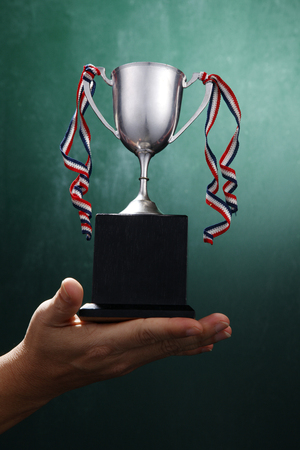 Human hand holding a silver trophy. 写真素材