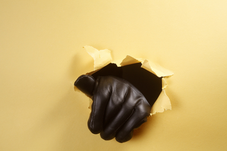 hand wiith leather glove breaking through the hole 写真素材