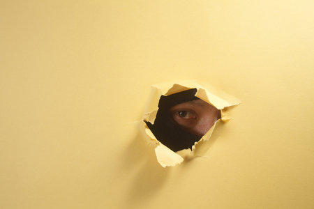 stock image of thief peeping through a hole 写真素材 - 117690535