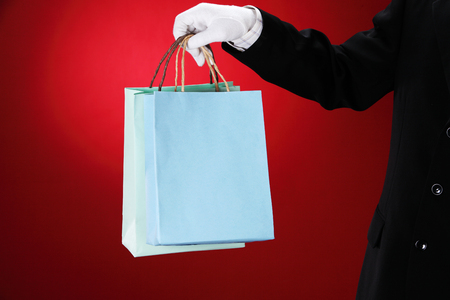 Doorman wearing white gloves, holding shopping bags