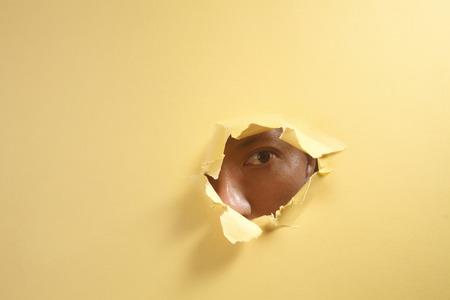 stock image man peeping through a hole