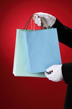 Doorman wearing white gloves, holding shopping bags