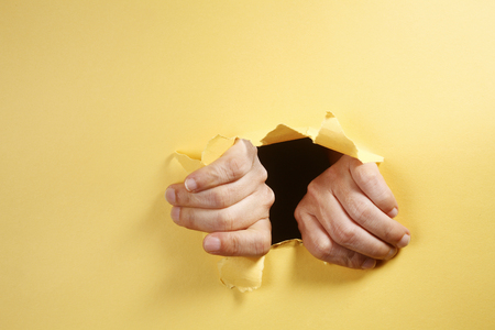 stock image of the hands breaking through a hole