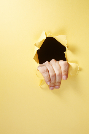 stock image of the hand breaking through a hole