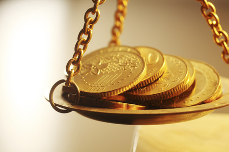 stacks of bright new shiny gold coins placed on weighing scales