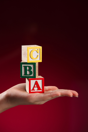 child holding toy alphabet blocks in palm of hand