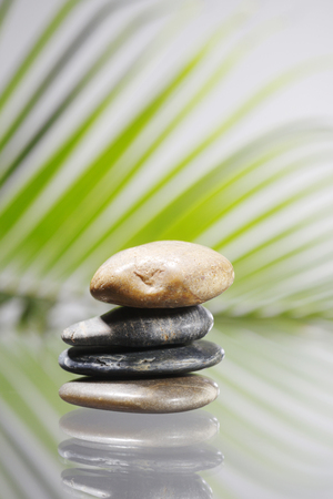 stack of the stone in front of palm leaf