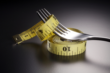 fork and measuring tape on the gray background Stock Photo