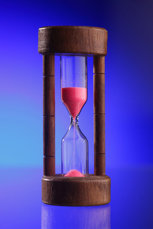 Close up of the hourglass on the blue background Stock Photo