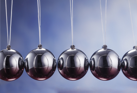 Newton's cradle against blue background Stock Photo