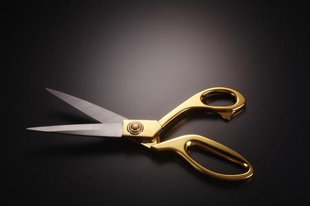golden scissors on the gray background