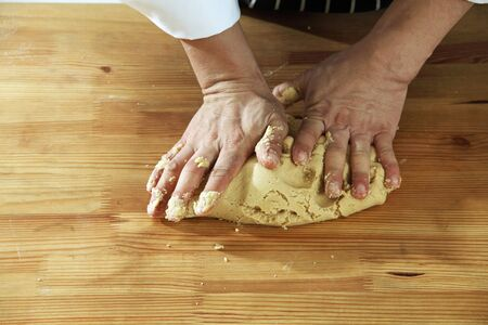 hands in flour closeup kneading dough on table
