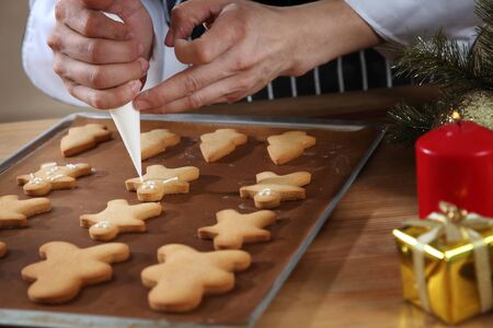 close up of the chef decorating cookies with icing sugar