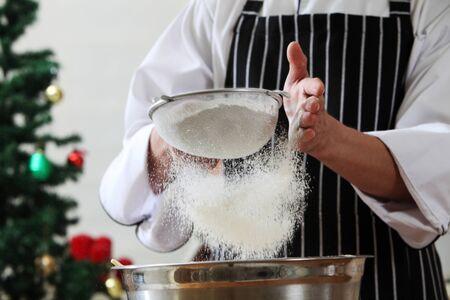 caster sugar sifting through a sieve for a baking