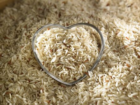 brown rice and glass heart shape container 스톡 콘텐츠