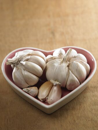 Garlic in a heart shaped bowl 스톡 콘텐츠