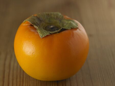 close up of the persimmon on the wooden background