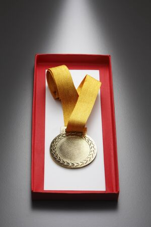 gold color medal in a box Imagens