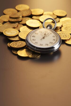 stop watch on pile of gold coin